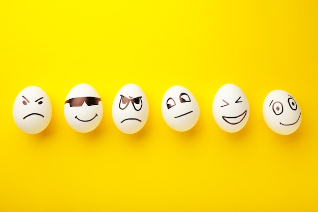 Śmieszne pisanki z różnymi emocjami na twarzy na żółtym tle.
