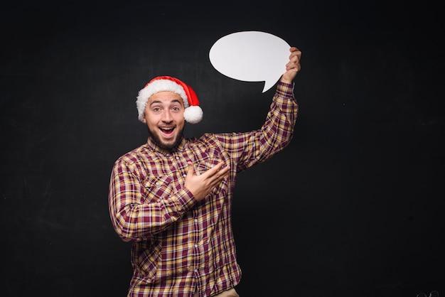 Śmieszne poważne człowiek w czerwonym kapeluszu christmas santa trzyma pusty biały karton jako puste lub makiety z miejsca kopiowania tekstu. czarne tło