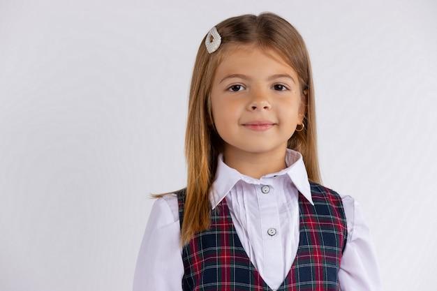 Śmieszne pozytywne dziecko w szkole podstawowej dziewczyna z długimi włosami na sobie mundur na białym tle na białej ścianie. szczęśliwy uczeń kaukaski dziecko z bliska portret headshot.