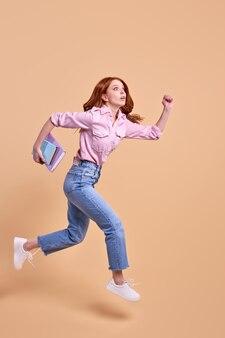 Śmieszne rude studentka pędzi do przodu z książką w rękach pospiesz się na uniwersytet ubrany dorywczo strój bieganie września egzamin na białym tle w studio pełnometrażowy portret