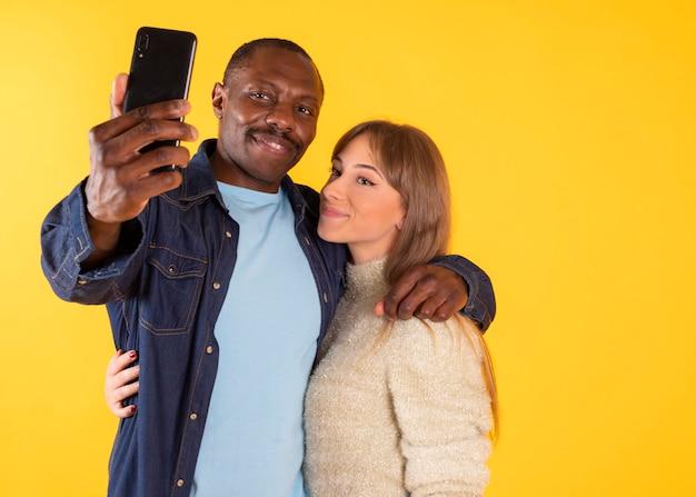 Śmieszne selfie. rozochocona międzyrasowa para krzywi się i pokazuje języki podczas robienia zdjęcia na smartfonie, pozuje,