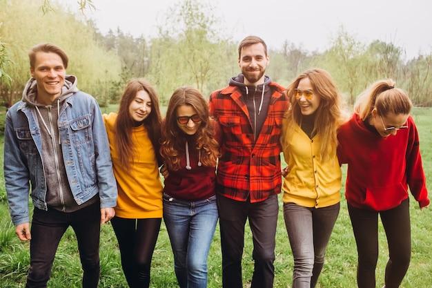 Śmieszne selfie z przyjaciółmi. towarzystwo wesołych przyjaciół robi selfie i uśmiecha się stojąc na zewnątrz. ludzie noszą czerwone i żółte swetry. młodzi ludzie odpoczywający w przyrodzie, rozmawiający i śmiejący się