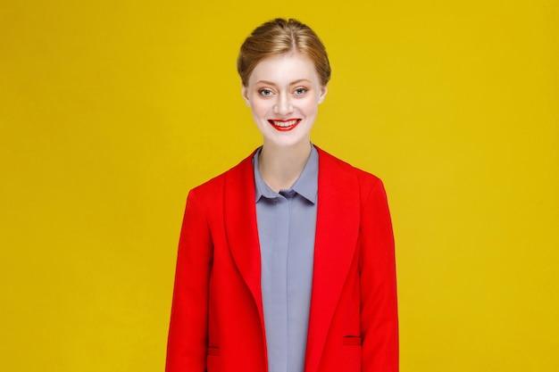 Śmieszne szczęście czerwona głowa modelu w czerwonym kolorze uśmiech ząb. studio strzał, odizolowane na żółtym tle