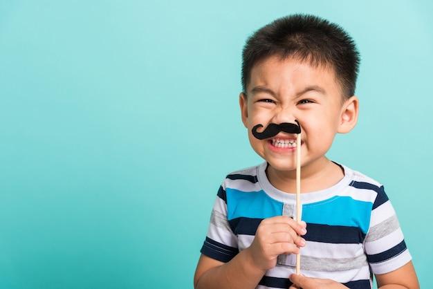 Śmieszne szczęśliwe dziecko hipster trzyma czarne wąsy rekwizyty do fotobudki blisko twarzy