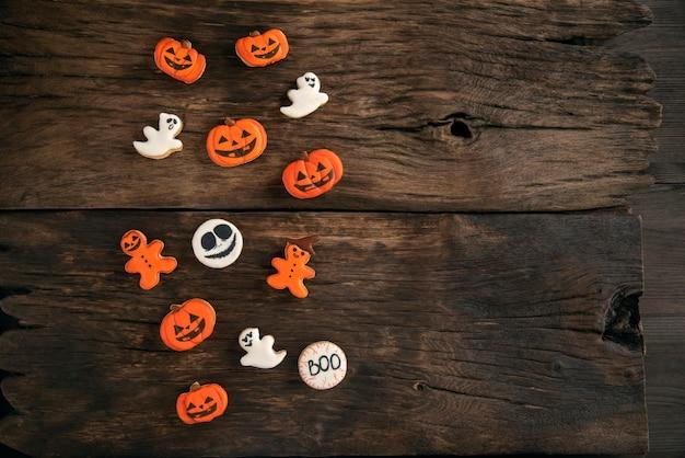 Śmieszne tło na halloween z mieszanki pomarańczowych i białych ciasteczek na brązowym drewnianym stole. skopiuj miejsce