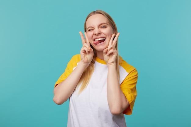 Śmieszne ujęcie młodej atrakcyjnej blondynki długowłosej pani oszukuje i pokazuje język, patrząc na kamery, pokazując znak zwycięstwa stojąc na niebieskim tle