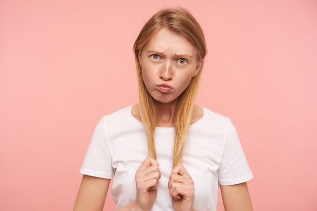 Śmieszne ujęcie młodej zielonookiej długowłosej rudowłosej kobiety ubranej w białą koszulkę podstawową, która ściąga usta i wykrzywia twarz, wygłupiając się na różowym tle