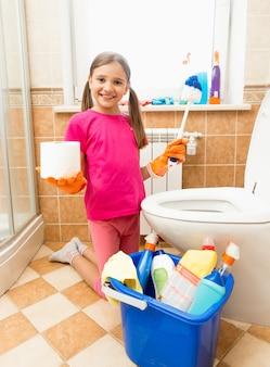 Śmieszne ujęcie uśmiechniętej dziewczyny pozującej z papierem toaletowym i pędzlem w łazience