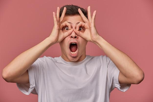 Śmieszne ujęcie w pomieszczeniach atrakcyjnego młodego ciemnowłosego mężczyzny w zwykłych ubraniach stojącego na różowym tle, śmiejącego się i trzymając podniesione ręce w twarz, patrząc na aparat z szeroko otwartymi oczami i ustami
