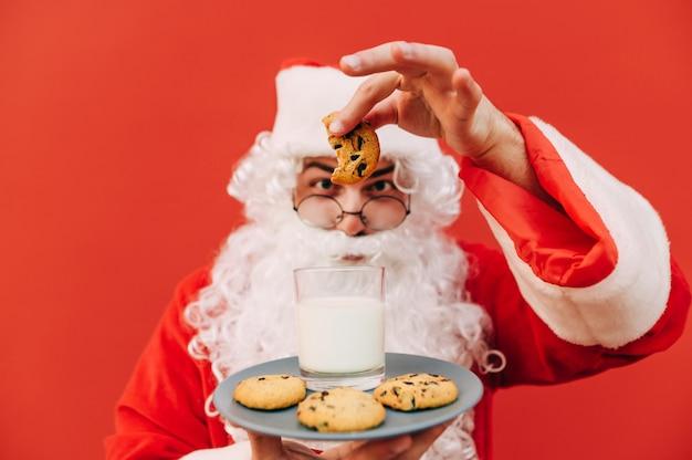 Śmieszne ujęcie wesołego starego mikołaja trzymającego talerz z ciasteczkami
