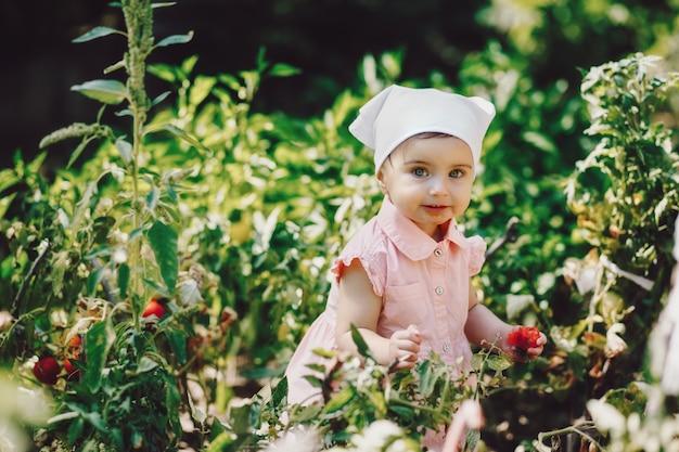 Śmieszne, urocze dziecko z białą chustką je pomidora w ogrodzie i uśmiecha się do kamery