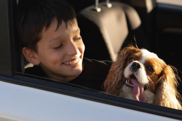 Śmieszne zdjęcie chłopca nastolatek uśmiechający się patrząc przez okno samochodu ze swoim psem cavalier king charles spaniel, zamierza wybrać się na wycieczkę