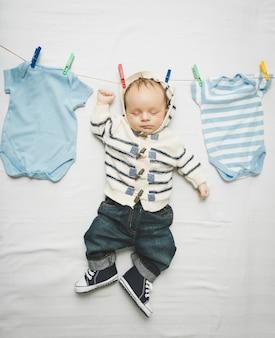 Śmieszne zdjęcie małego chłopca w dżinsach wiszącego na sznurku obok suszenia ubrań