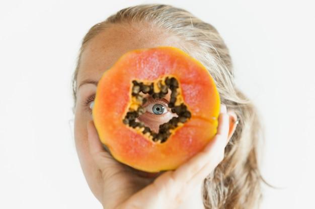 Śmieszne zdjęcie pozytywnej młodej kobiety z uśmiechniętą twarzą, trzymając w rękach dojrzałe owoce tropikalne - plasterek papai pomarańczowy