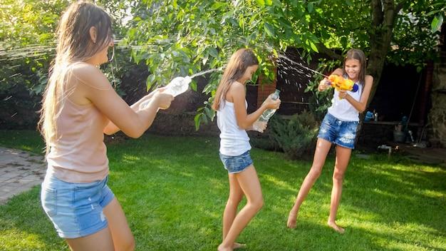 Śmieszne zdjęcie szczęśliwej rodziny z dziećmi bawiącymi się i chlapiącymi wodą pistoletami na wodę i wężem ogrodowym w upalny słoneczny dzień