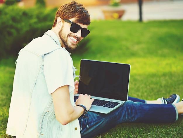 Śmiesznego uśmiechniętego modnisia faceta przystojny mężczyzna w stylowym lecie odziewa na ulicznym obsiadaniu na trawie w parku z notatnikiem
