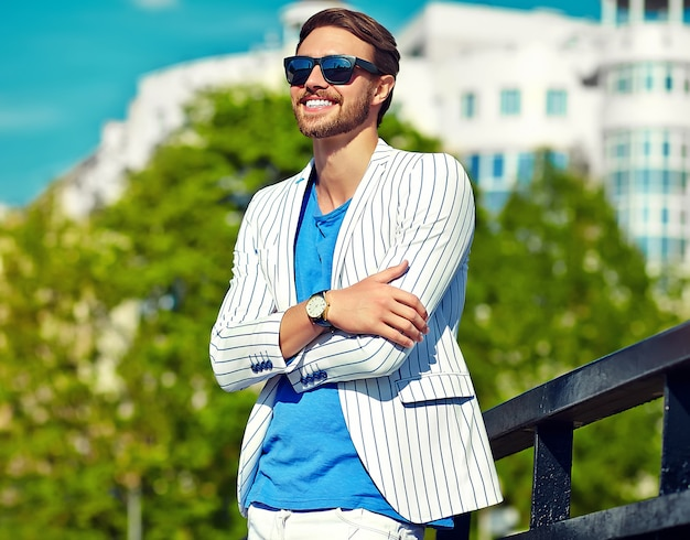 Śmiesznego uśmiechniętego modnisia przystojny mężczyzna w stylowego lata białym kostiumu pozuje w ulicie w okularach przeciwsłonecznych