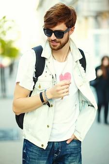 Śmiesznego uśmiechniętego modnisia przystojny mężczyzna w stylowym lata płótnie na ulicy w okularach przeciwsłonecznych