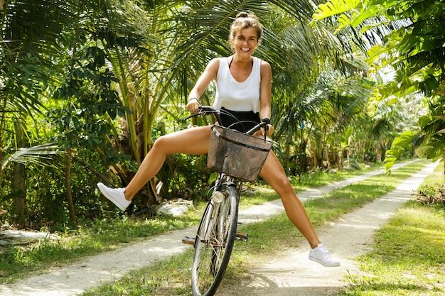 Śmiesznej kobiety jeździecki bicykl w tropikalnym ogródzie