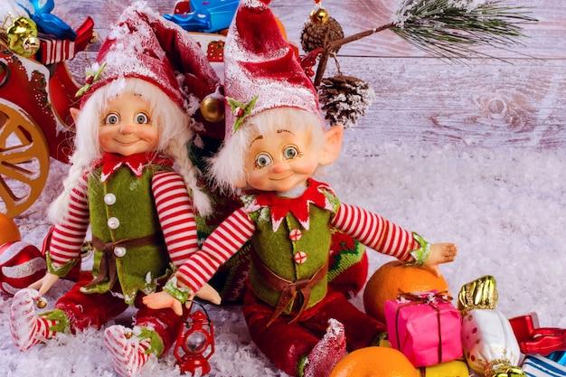 Śmieszni boże narodzenie elfy siedzą obok bożenarodzeniowej skarpety na lekkim drewnianym tle.