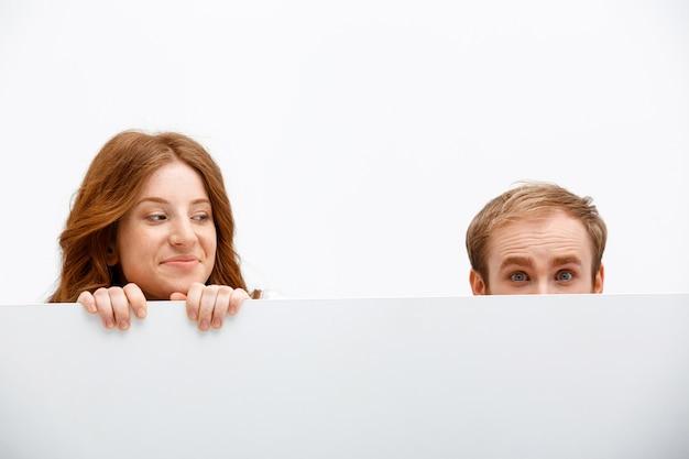 Śmieszni dorosli rudzielec mężczyzna, kobieta chuje za stołem i