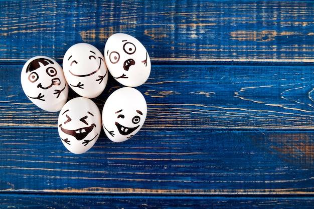 Śmieszni easter jajka z różnymi śmiesznymi twarzami na błękitny drewnianym