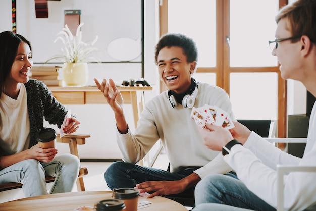 Śmieszni faceci grają w karty z przyjaciółmi w domu