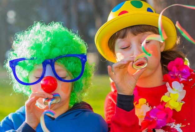 Śmieszni karnawałowi dzieciaki uśmiecha się plenerowego i bawić się