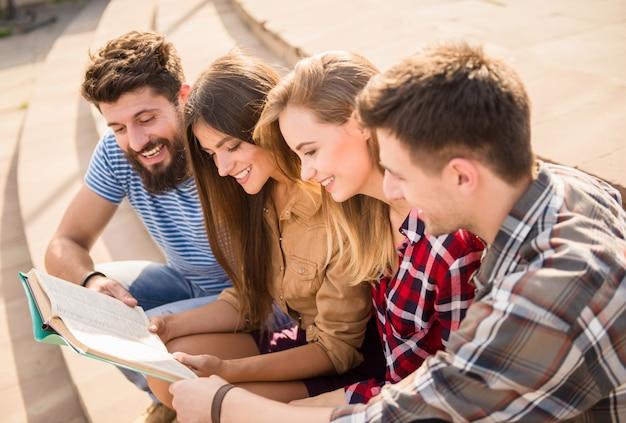 Śmieszni ludzie czytają razem jedną książkę.
