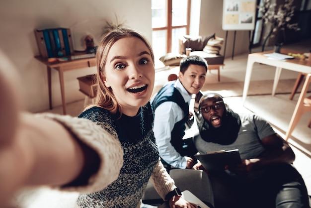 Śmieszni młodzi ludzie biorą fotografii pracę w biurze