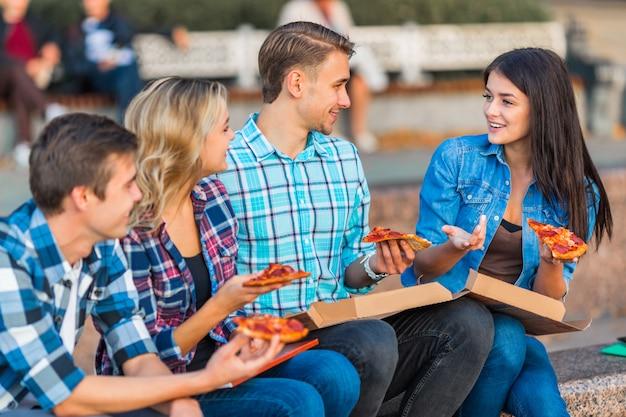 Śmieszni młodzi ucznie jedzą pizzę w parku.
