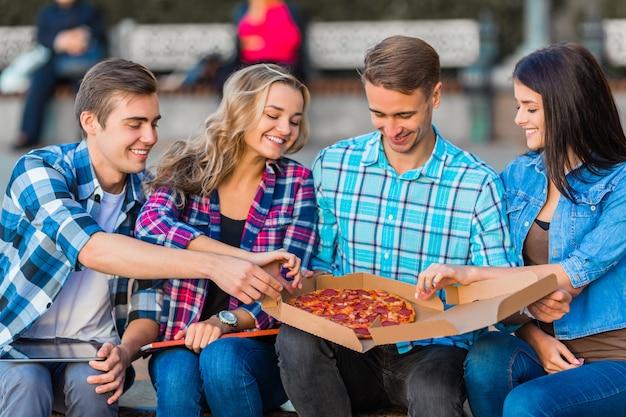 Śmieszni młodzi uczniowie jedzą pizzę.