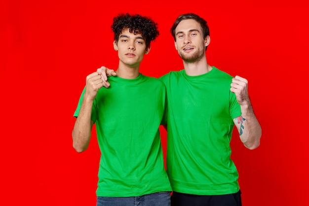 Śmieszni przyjaciele z zielonymi koszulkami na czerwonej ścianie