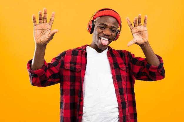 Śmieszny amerykański murzyn z grymasem na twarzy słucha muzyki na żółto