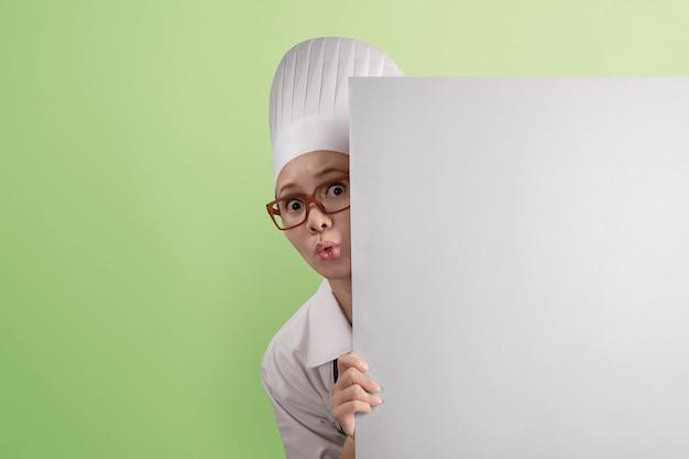 Śmieszny azjatykci kobieta szefa kuchni zerkanie od behind pustego copyspace