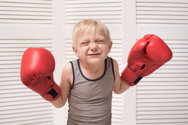 Śmieszny blond chłopiec w czerwonych bokserskich rękawiczkach. pojęcie sportu
