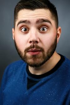 Śmieszny brodaty mężczyzna o piwnych oczach wygląda na nietkniętego
