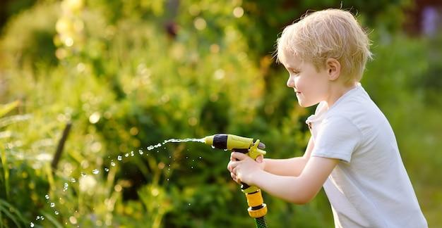 Śmieszny chłopiec bawić się z ogrodowym wężem w pogodnym podwórku