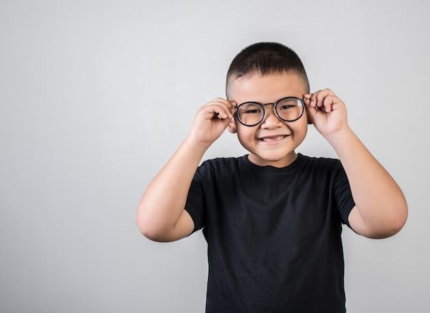 Śmieszny chłopiec geniusz jest ubranym szkła w studio strzale