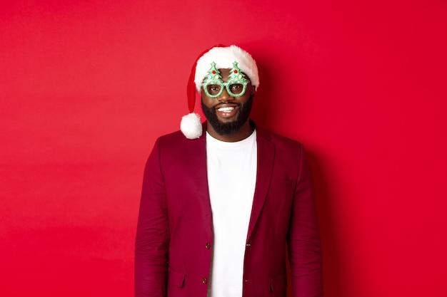Śmieszny czarny człowiek w santa hat i party okulary świętuje boże narodzenie, uśmiechając się szczęśliwy i życząc wesołych świąt, stojąc na czerwonym tle.
