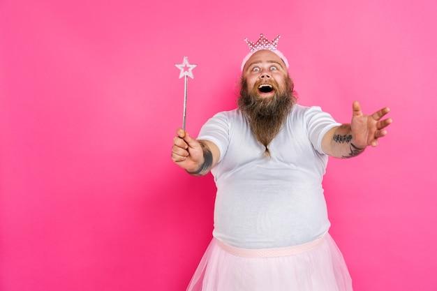 Śmieszny grubas udając baletnicę z tutu na różowej ścianie