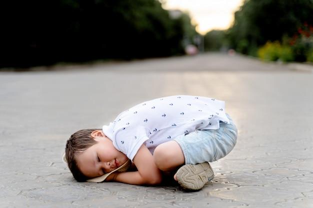 Śmieszny mały chłopiec leży na podłodze