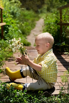 Śmieszny mały chłopiec siedzi na moście z stokrotkami
