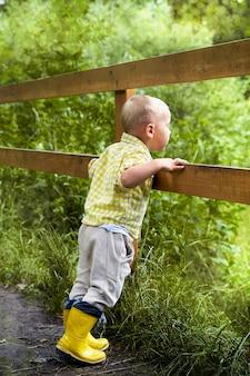 Śmieszny mały chłopiec w żółtych butach wygląda przez płot. lato
