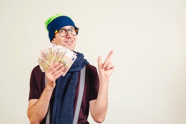 Śmieszny mężczyzna jest ubranym chodnikowa mienia pieniądze w szkłach i wskazuje na pustej kopii przestrzeni. męski głupek z banknotami na bielu. mężczyzna przedstawia produkt lub pomysł