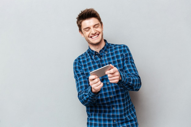 Śmieszny mężczyzna śmia się podczas gdy bawić się z smartphone