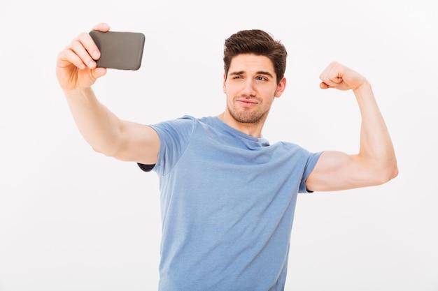 Śmieszny mężczyzna w koszulce robi selfie na smartphone podczas gdy pokazywać jego biceps nad szarości ścianą