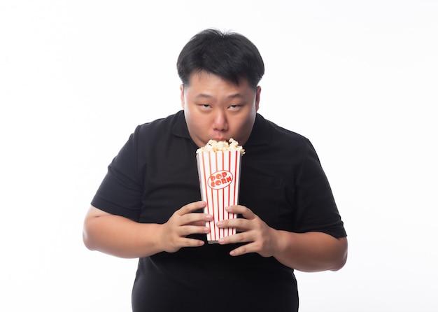 Śmieszny młody azjatykci gruby mężczyzna w czarnym polo koszula je popkorn odizolowywającego nad białym tłem