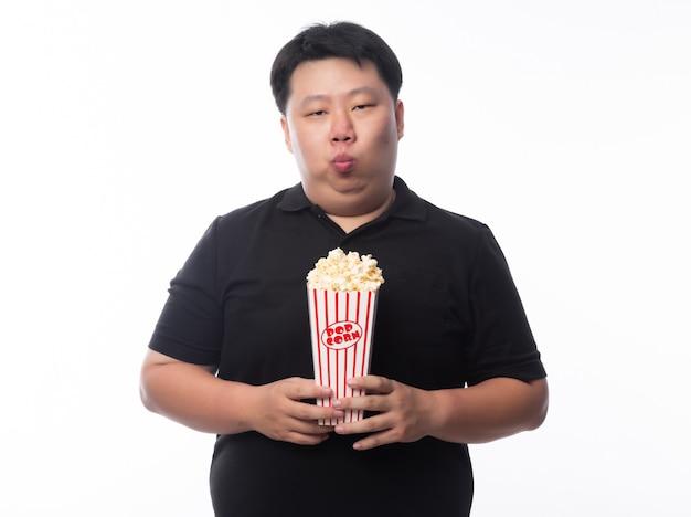Śmieszny młody azjatykci gruby mężczyzna w czarnym polo koszula mienia popkornie odizolowywającym nad białym tłem