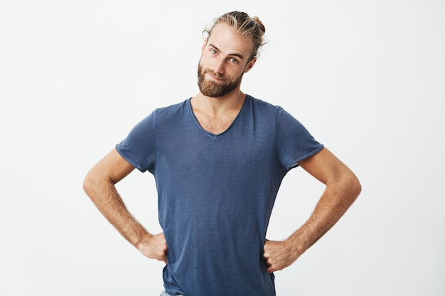 Śmieszny przystojny mężczyzna z modną fryzurą i brodą, trzymając się za ręce w pasie